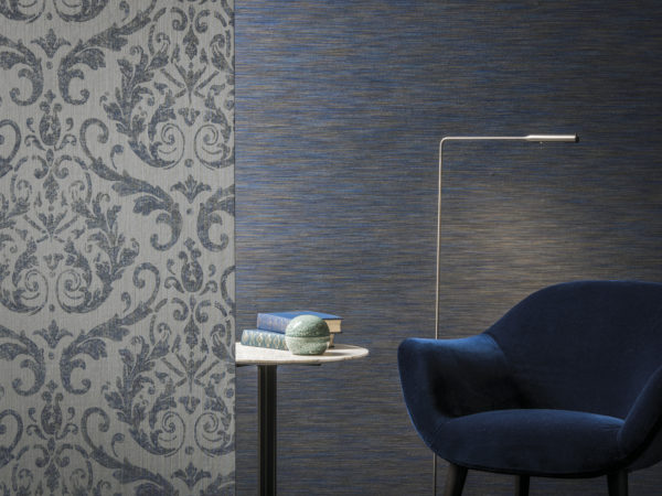 Tactile room with elegant damask wallcovering and dark bleu space dye wallcovering. A velvet seat and reading light invite to lounge. The Omexco Elegance collection.
