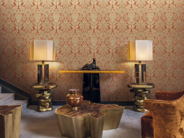Tactile room with brown armchair and golden lamps and centre table. Eyecatching gold and orange damast wallcovering by Gala.