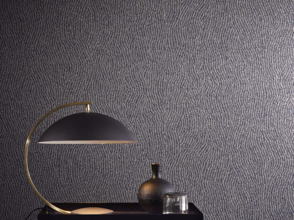 The mica wallcovering in this picture is printed with a weavy geometrical pattern. It's combined in this interior with a geometrical black lamp and vase.