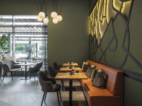 Image displaying Omexco's High Performance Textures wallcovering. 'Abaca' is the name of the design. The green non-woven wallcoverings are shown horizontally on the walls of this contemporary restaurant.