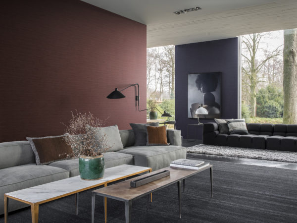 Living room with large windows overlooking a garden with a large tree. Contemporary furniture in grey tones. Green vase with pink blossoms. On the wall Omexco Portfolio wallcoverings in red and blue. On the blue wall a blue picture of a girl with an afro.