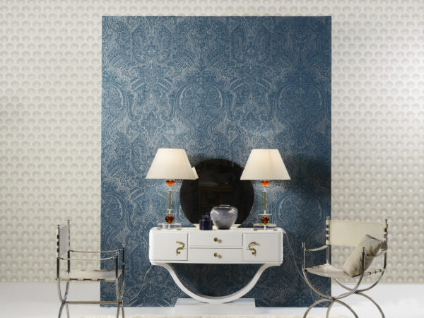 Like the gardens of Shalimar, near Lahore (Pakistan), the wallcovering collection Shalimar of Omexco took inspiration from the fusion of arab and persian influences. In this interior the round motif is combined with the stunning arab blue damask. We see a white console with snake handles.