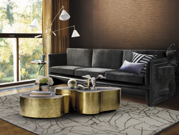Decorative living room with black sofa, gold center table and large window. Behind the sofa copper Vogue wallcovering.