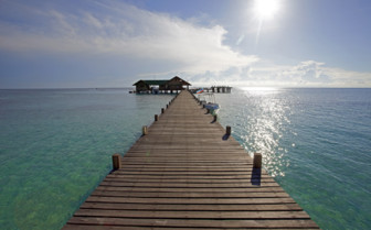 Long jetty with blue water looking into the sun