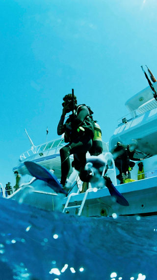 Diver jumping off boat