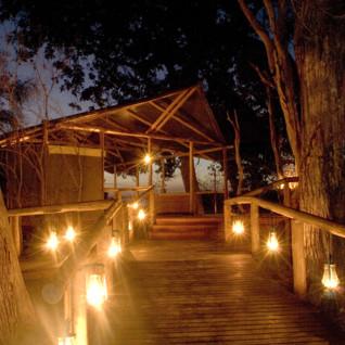 Camp exterior at night at Little Kwara Camp, luxury camp in Botswana