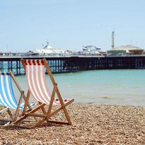 Two deckchairs overlooking Brighton Pier