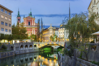 beautiful photograph of buildings and a bridge in ljubljana at dusk