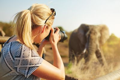 Woman taking a photo of an elephant on safari