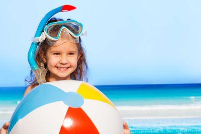 a happy young girl with a large beach ball