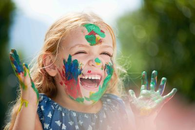 a laughing girl with paint on her face