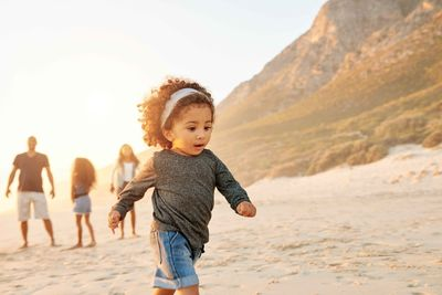 young girl playing and running on the beach