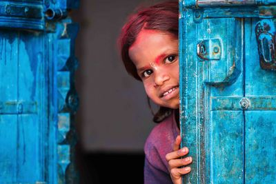 a small girl hiding behind a door in India