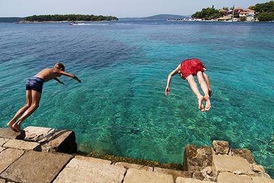 boys diving into the sea