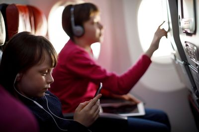 children watching films on an airplane