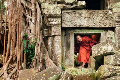 a monk climbing out of a temple
