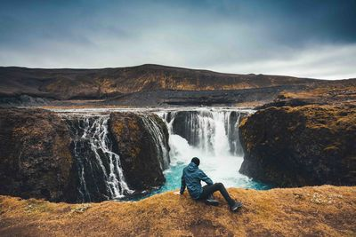 man sitting in front of waterfall