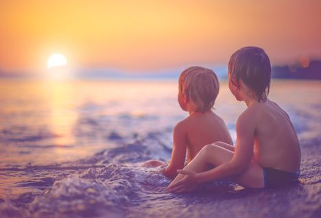 boys on a beach at sunset