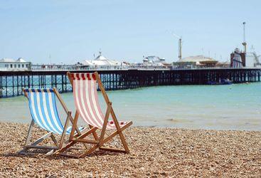 Two deckchairs overlooking Brighton Pier