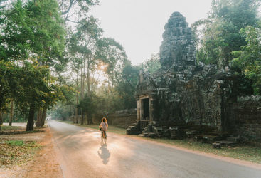 Woman riding bicycle in Angkor Wat