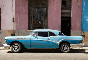 A blue classic car against a pink wall
