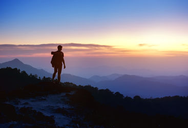 Man stands along on a mountain top at sunset