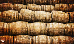 Traditional wooden barrels stacked up in a whisky distillery