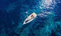 Sail boat aerial with crystal clear water surrounding