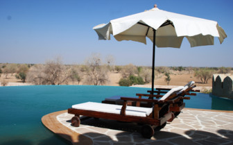 The hotel pool at Mihir Garh, luxury hotel in India