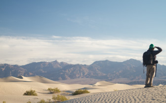 Man looking across the desert to the mountains