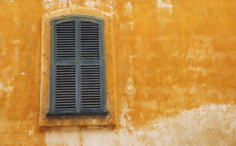 A Shuttered Window on a Yellow Wall