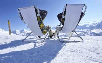 Two deck chairs in the snow