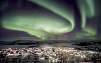 The Aurora Borealis over a Town in Swedish Lapland