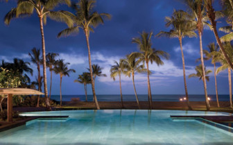 The pool at night at Four Seasons Resort Hualalai, luxury hotel in Hawaii