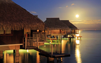 Night view of over water bungalows at the Hilton Moorea Resort