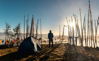 A camper at sunrise amongst prayer flags