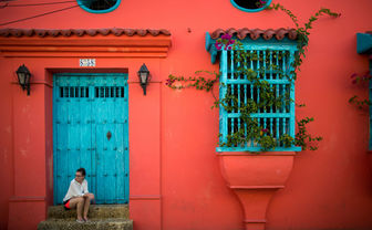 Woman sat on a bright red doorstep