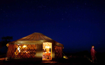 The tent exterior at night at the camp
