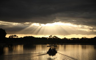 Boat cruises on the lake by sunset