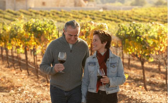 Couple in a vineyard with glasses of wine