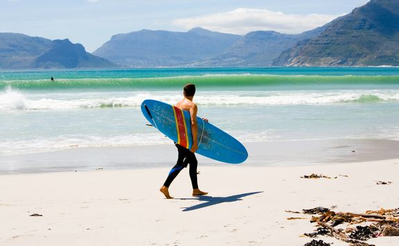 Man with surfboard on Kommetjie beach