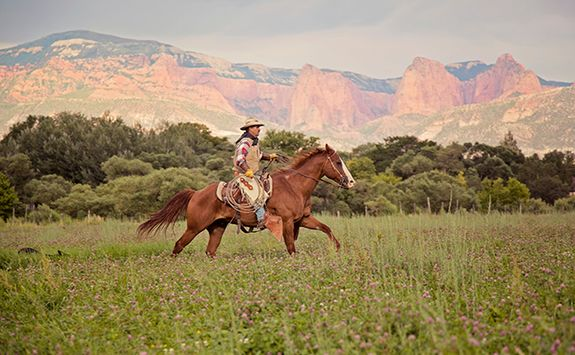 gaucho riding with mountains behind