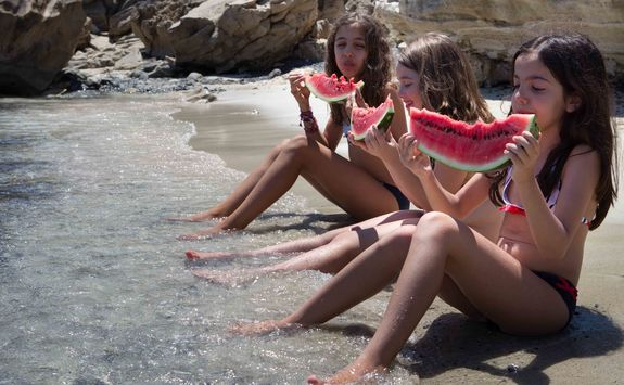 girls eating watermelons on a beach