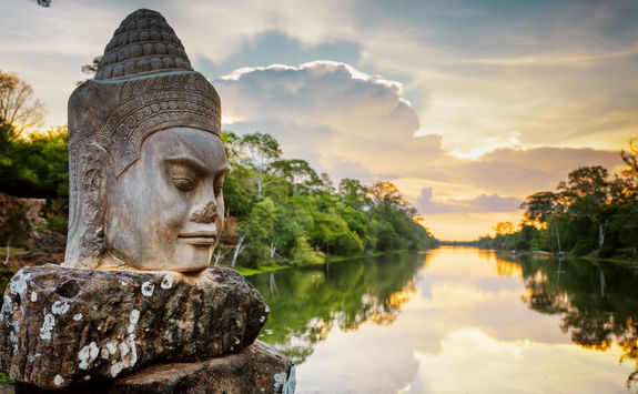 Stone face Asura and sunset over Angkor Thom