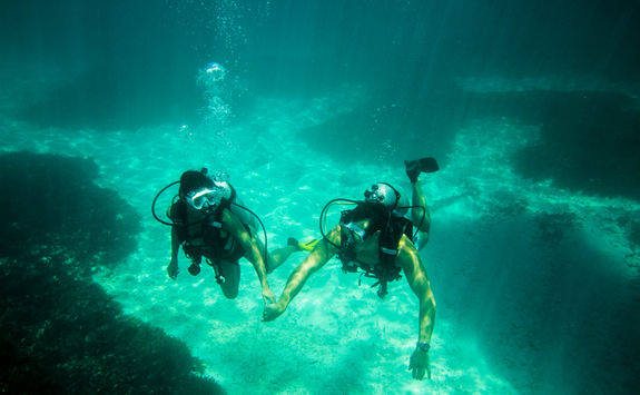 couple diving underwater