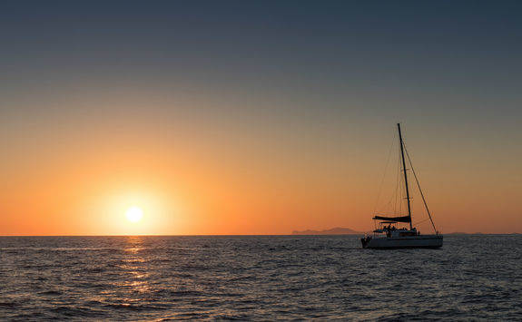 Catamaran out at sea at sunset