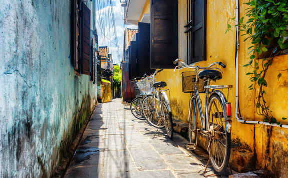 bicycles parked near yellow wall
