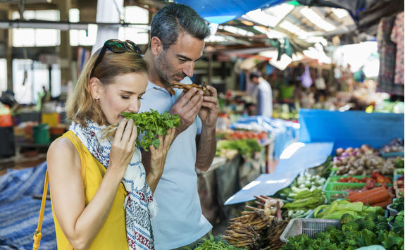 Couple smelling vegetables in a street market