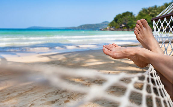 Feet in a hammock on a sand beach