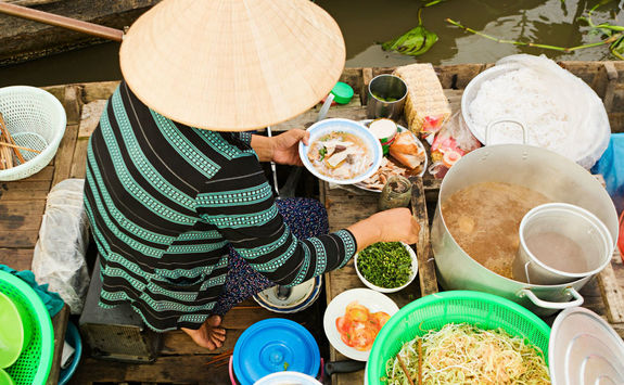 vietnamese woman preparing pho noodle soup on floating boat